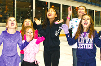 Girls having fun at an ice skating birthday party.