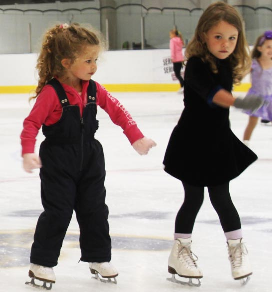 2 girls learning how to skate at beginner ice skating lessons.