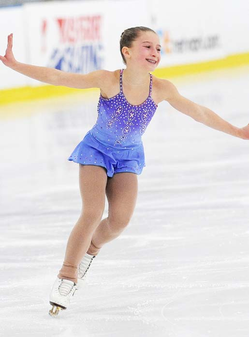 A skater in a purple dress practicing a routine during ice skating lessons.