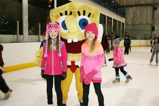 Two girls take a picture with Spongebob at public ice skating.