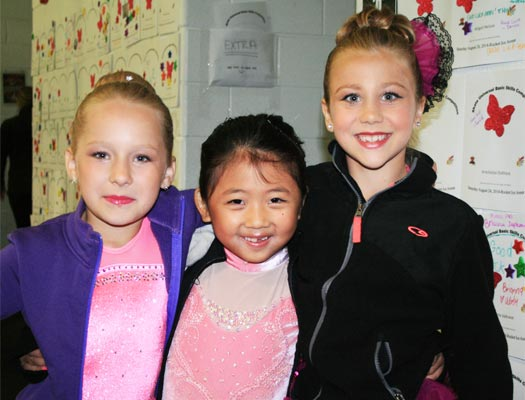 Three young figure skaters in full make-up ready to compete in the basic skills ice skating competition.