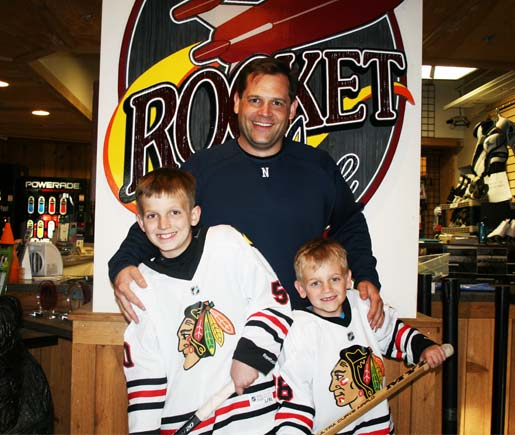 After a Hockey Training Session at Rocket Ice Skating Rink's Stick and Puck a dad poses with his two sons.