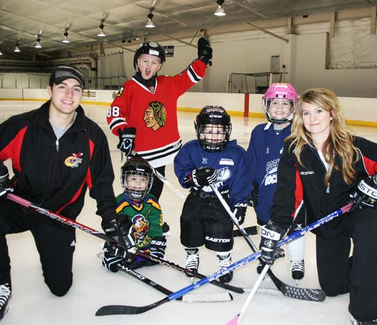 Four hockey players and two instructors posing for a picture after hockey lessons