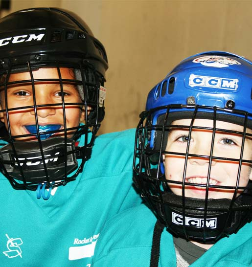 Two friends from hockey lessons smile for the camera in their hockey helmets