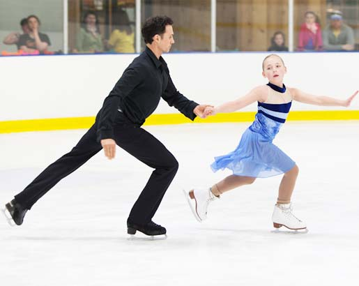 Coach and student practice routine during freestyle ice skating times