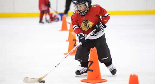 Youth hockey player working on his skating and stick handling in hockey training.