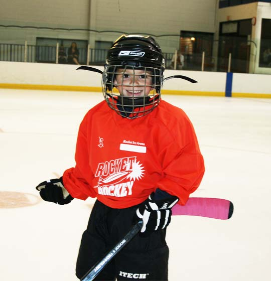 Young skater at hockey lessons smiling with hockey stick