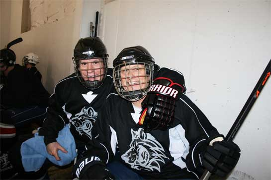 Two over 50 year old men sitting on bench during an adult hockey league game