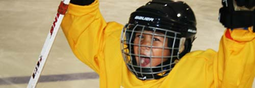 After winning a game during hockey lessons boy in yellow Rocket Ice Skating Rink jersey celebrates