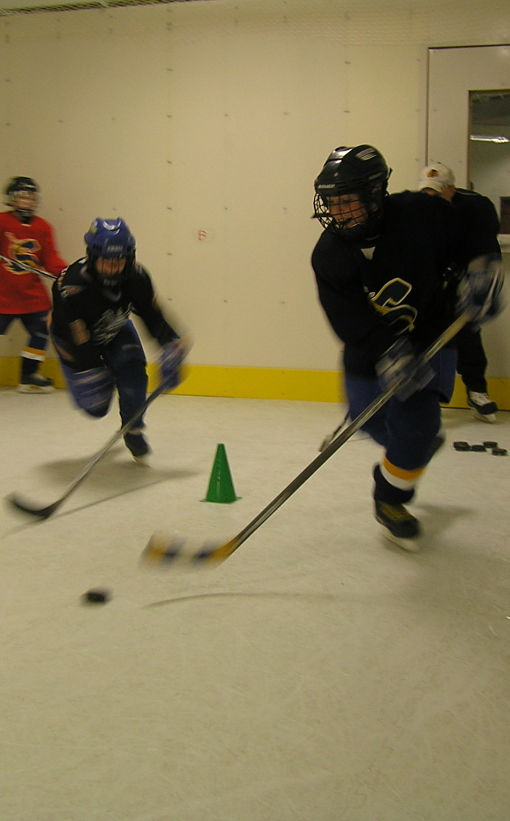 Group of students hockey practice on synthetic ice.