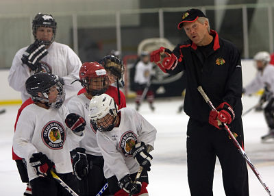 Blackhawks youth hockey group being instructed by alumni on the ice.